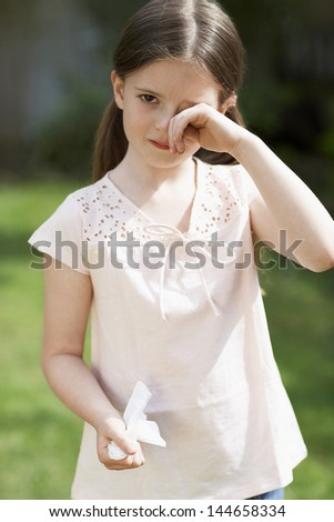 Portrait of young girl with cold rubbing eyes in backyard - stock photo