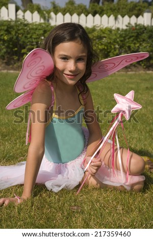 Portrait of young girl with fairy wings and wand - stock photo