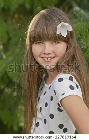 Portrait of young girl with flower in her hair - stock photo