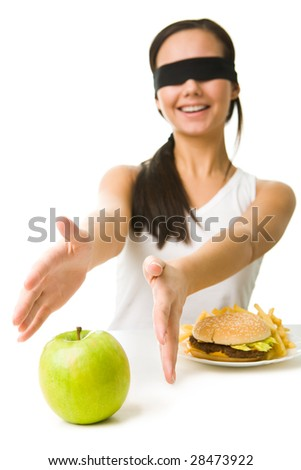 Portrait of young girl with her eyes folded stretching her arms towards green apple - stock photo