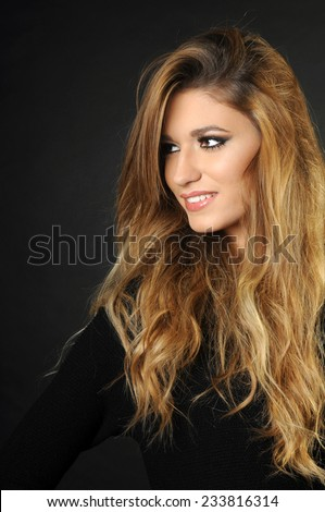 portrait of Young girl with long perfect hair smiling and looking away isolated on black