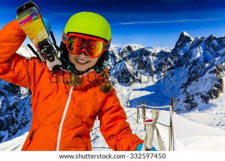 Portrait of young girl with ski, in background panorama of snowy Alps Mountains - stock photo