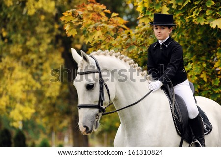 Portrait of young girl with white dressage horse