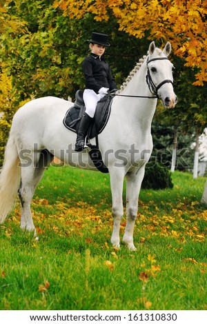 Portrait of young girl with white dressage horse - stock photo
