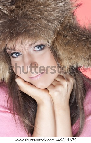 Portrait  of young girls in a fur cap on a pink background - stock photo