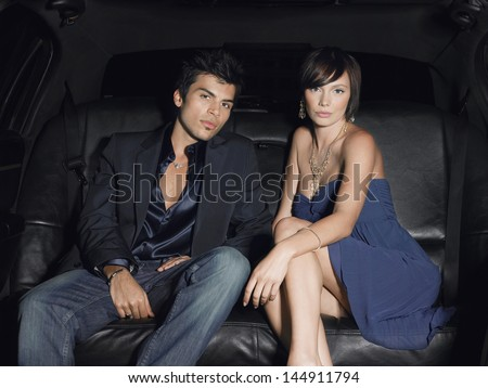 Portrait of young glamorous couple in limousine