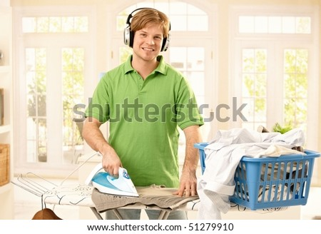 Portrait of young goodlooking man with headphones ironing clothes in living room, looking at camera, smiling. - stock photo