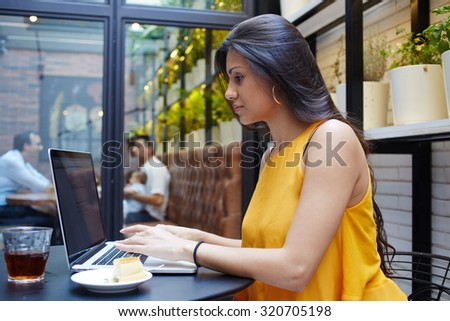 Portrait of young gorgeous businesswoman working on her laptop in coffee shop, charming long brunette hair female keyboarding on her net-book while sitting in cozy restaurant during lunch break - stock photo