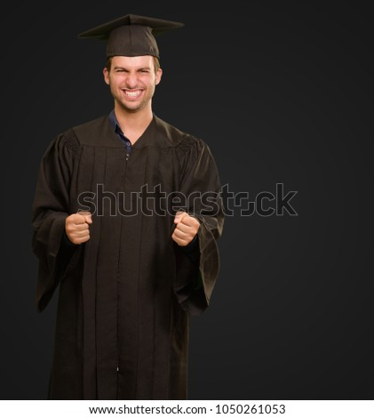 Portrait Of Young Graduation Man Isolated On Black Background