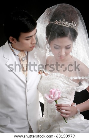 Portrait of young groom looking to his bride - stock photo