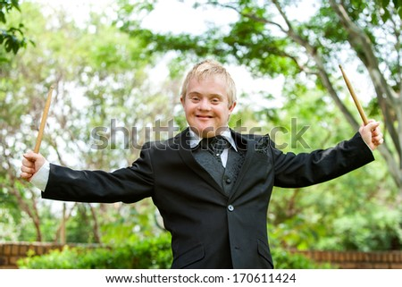 Portrait of young handicapped drummer with arms open outdoors. - stock photo