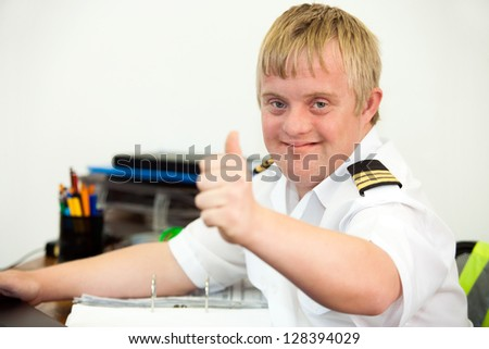 Portrait of young handicapped pilot showing thumbs up at office desk.