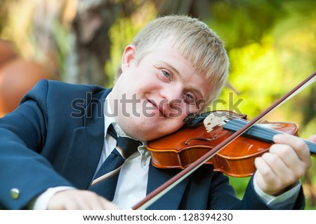 Portrait of young handicapped violinist practicing outdoors.