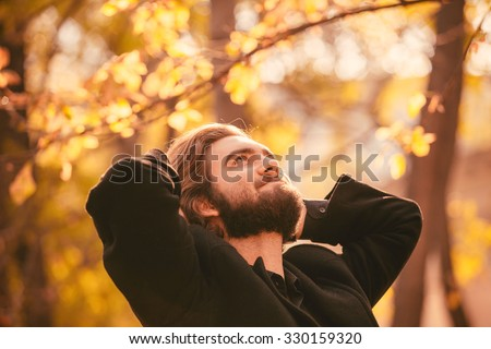 Portrait of young handsome bearded guy in the autumn city park. Enjoying of the moment of happiness. - stock photo