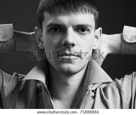 portrait of young handsome brunet guy posing in gray shirt on green - stock photo