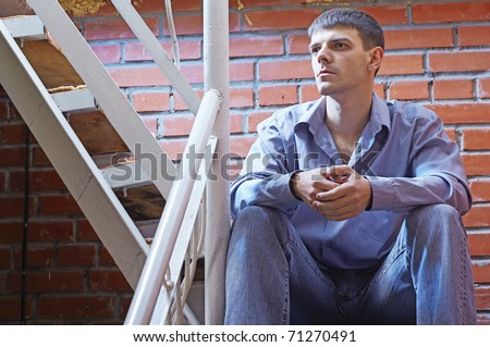 portrait of young handsome brunet guy posing near red brick wall - stock photo
