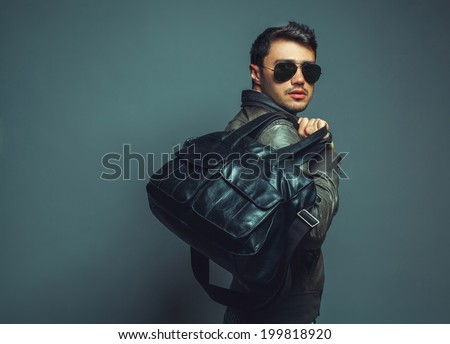 Portrait of young handsome fashion man with leather bag wearing sunglasses and leather jacket. Close up. Copy-space. Studio shot - stock photo