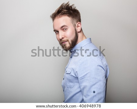 Portrait of young handsome friendly man in blue shirt. Studio photo on light grey background.