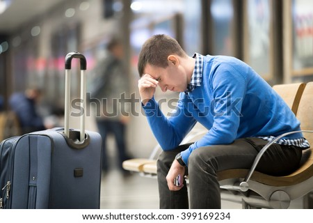 Portrait of young handsome guy wearing casual style clothes waiting for transport. Tired traveler man travelling with suitcase sitting with frustrated facial expression on a chair in modern station - stock photo