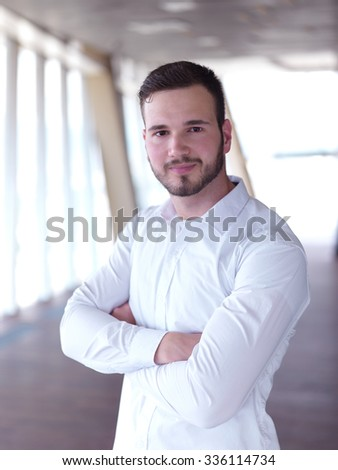 portrait of young handsome hipster business man with beard at modern office space interior