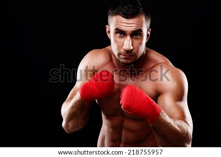 Portrait of young handsome male boxer in stance over black background