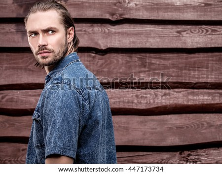 Portrait of young handsome man against wooden wall. - stock photo