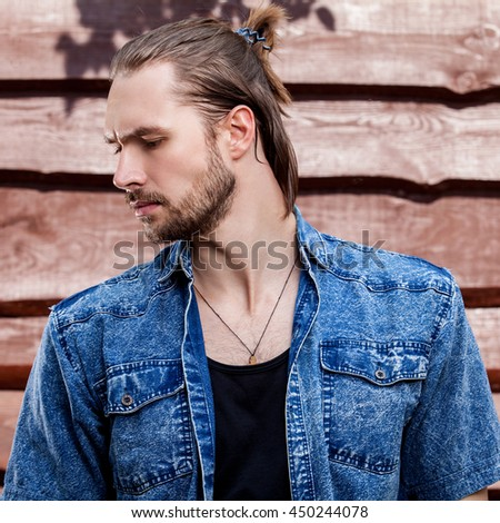 Portrait of young handsome man against wooden wall.
