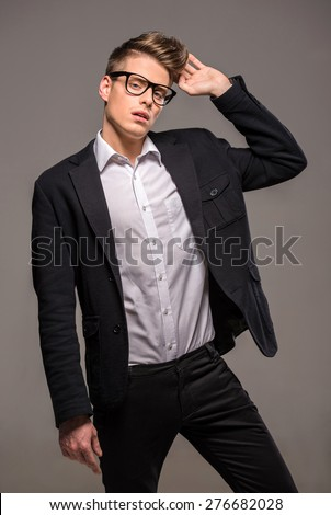 Portrait of young handsome man dressed casual posing in the studio on dark background. Fashion portrait. - stock photo