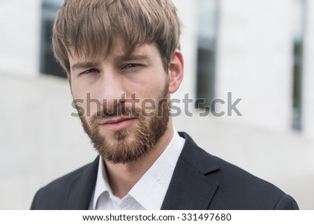 Portrait of young handsome man in black suit - stock photo