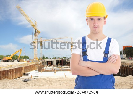 portrait of young handsome man in blue builder uniform