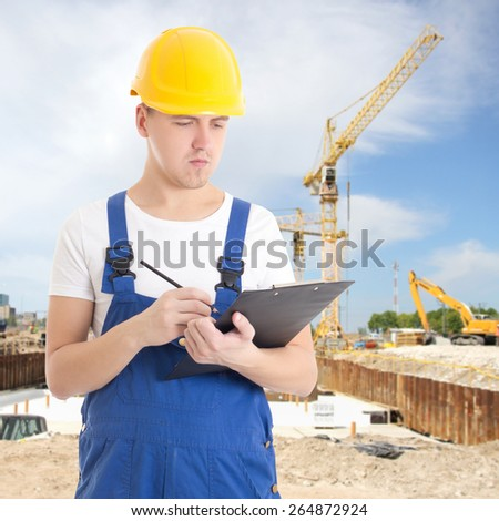 portrait of young handsome man in  builder uniform with clipboard at construction site