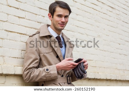 Portrait of young handsome man in cloak near the brick wall. Happy smiling men. Hands crossed on his chest. - stock photo