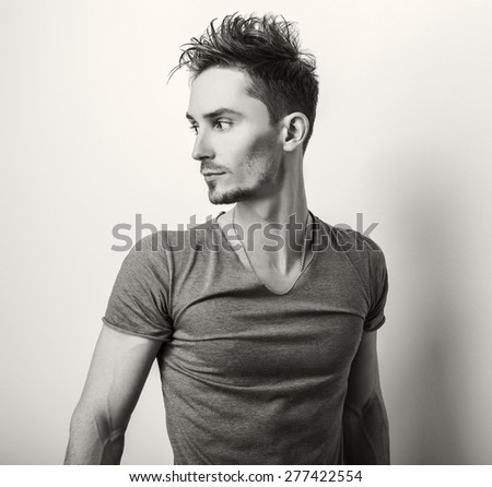 Portrait of young handsome man in grey t-shirt. Sepia studio photo.  - stock photo
