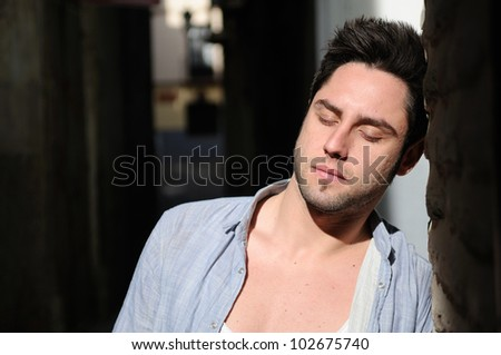 Portrait of young handsome man in urban background with eyes closed - stock photo