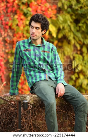 portrait of young handsome man sitting on stairs - stock photo