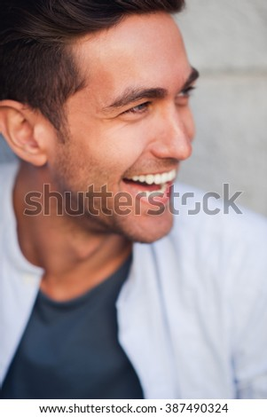 Portrait of young handsome man smiling and looking aside - stock photo