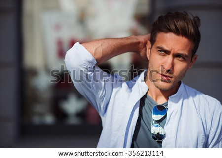 Portrait of young handsome man touching his hair and looking aside   - stock photo