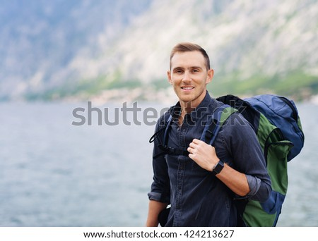 Portrait of young handsome man with backpack outdoor
