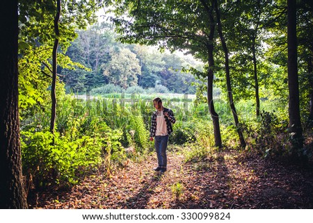 Portrait of young handsome man with backpack wanderer walk in the woods while enjoying the nature landscape, male hiker walking in mountain forest with plants, traveler hike in the mountains in summer - stock photo