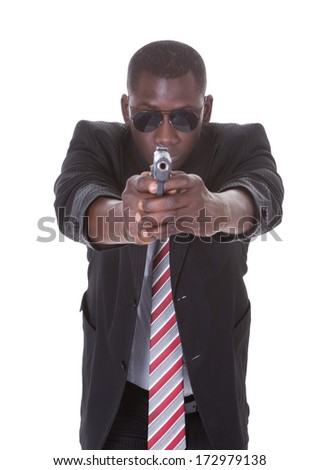 Portrait Of Young Handsome Man With Black Sunglasses And Gun