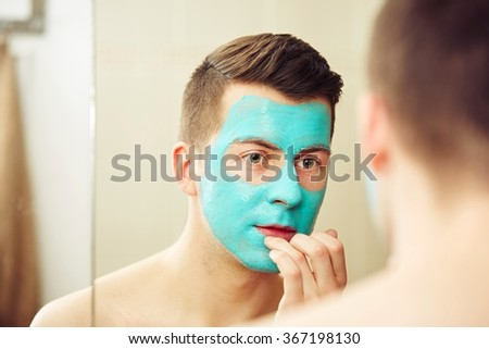 Portrait of young handsome man with facial mask. - stock photo