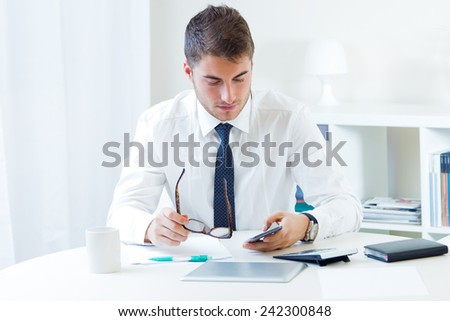 Portrait of young handsome man working in his office.