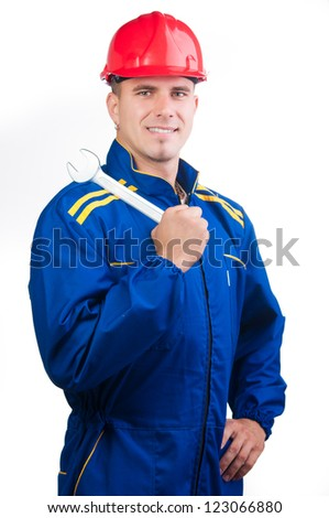 Portrait of young handsome mechanic with hard hat and in overalls holding wrench isolated on white. - stock photo