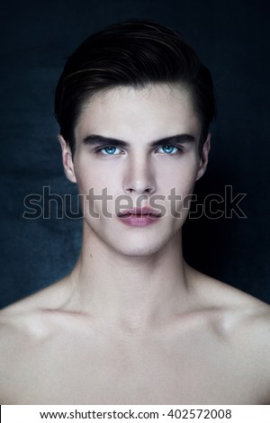 Portrait of young handsome naked man with blue eyes, looking at the camera. Dark background. - stock photo