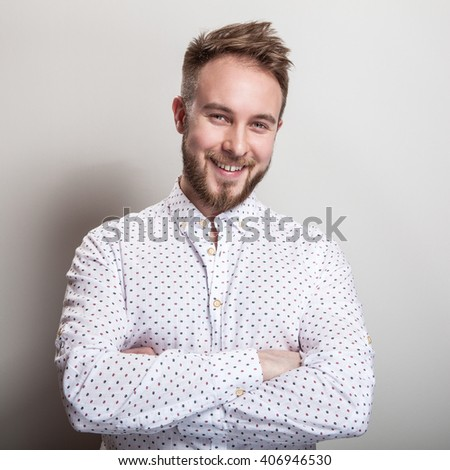 Portrait of young handsome positive man in white shirt with an amusing pattern.