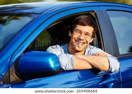 Portrait of young handsome smiling man in glasses looking out through open car window outdoor in sunny day - stock photo