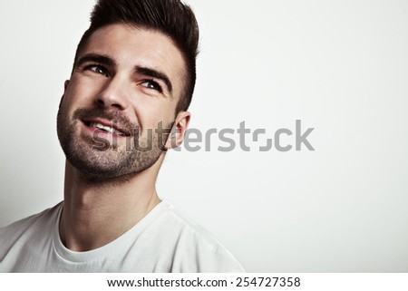 Portrait of young handsome smiling man with stubble