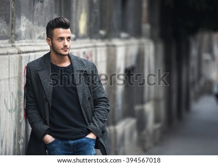 Portrait of young handsome stylish man in elegant coat. Outdoor fashion portrait.
