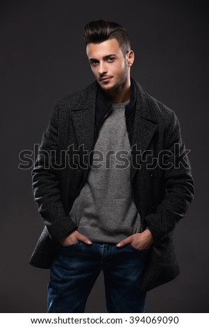 Portrait of young handsome stylish man in elegant coat. Studio fashion portrait.