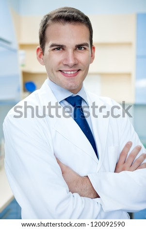 portrait of young handsome success doctor with arms crossed - stock photo